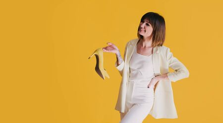 Beautiful young happy woman wearing trendy clothes posing with pair of yellow leather shoes on bright yellow background. Place for text. Copy space.