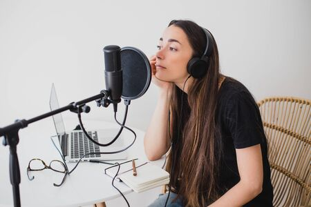Attractive young woman blogger with long black hair recording online podcast using her laptop, headphones and professional microphone.