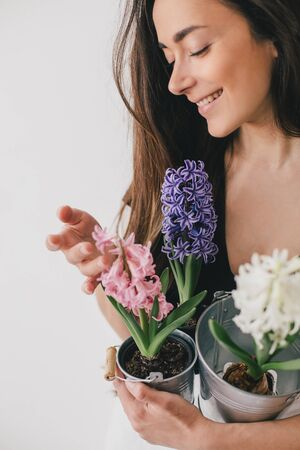 Young beautiful woman with long hair holding pots with hyacinth flowers on white background. Home gardening.