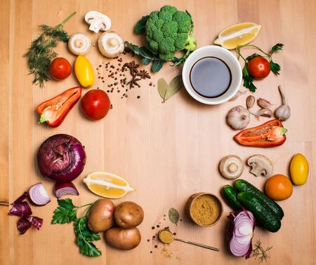 flavouring: Colorful salad ingredients on rustic wooden background with copy space, round frame, top view. Fresh vegetables mushrooms greens and spices around free copyspace. Healthy food concept. Stock Photo