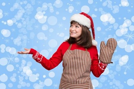 Portrait of attractive girl in chef apron, oven glove and christmas hat showing pointing on copyspase for your text on holiday background.