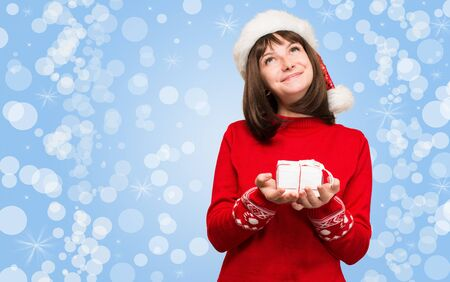 Girl in santa hat with Christmas gift in her hand dreaming smiling and looking up. Stock Photo