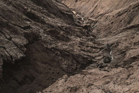 Dark Aged Shabby Landslip Surface Divided By Huge Cracks And Layers. Coarse Brown Mud And Clay Or Rock Texture Of Mountains, Background And Space For Text On Theme Geology And Mountaineering Concept. 版權商用圖片