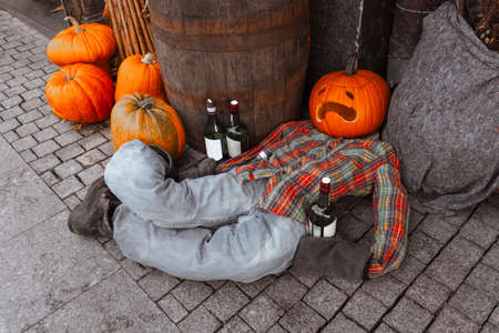Carved pumpkin head man laying on sidewalk with alcohol bottles. Creative halloween party outside decoration. Jack o lantern costume.