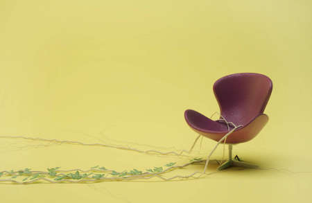 purple leather chair entwined with ivy on a yellow background