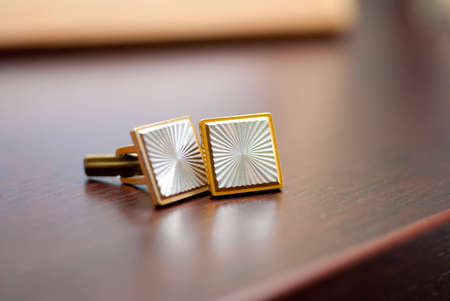 Cufflinks lying on a wooden table