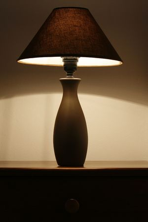 bedside table: an open bedside table lamp in a bedroom