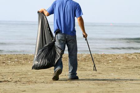 manos limpias: la contaminaci�n del medio ambiente de limpieza en la playa temprano en la ma�ana