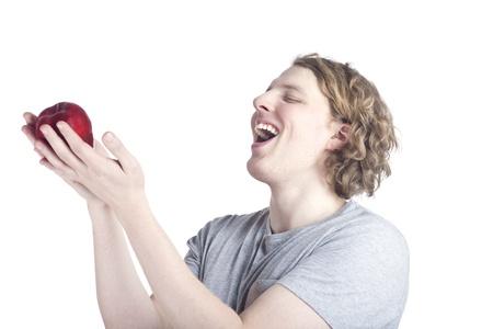 cherishing: Blonde casual young man cherishing an apple