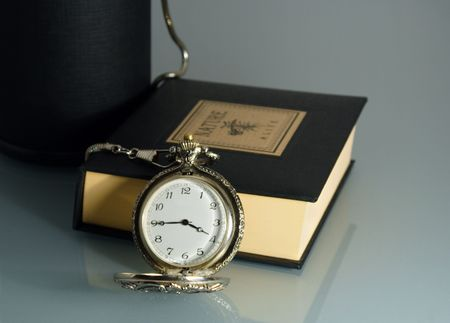 pocket watch and book on glass table photo