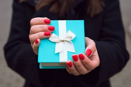Beautiful blue gift box with a white ribbon in the hands of a girl with a red manicure in a black coat in a city park.