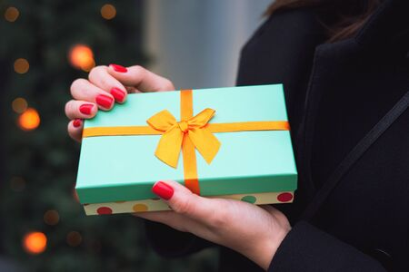 Beautiful turquoise gift box with an orange ribbon on the background of Christmas decorations in the hands of a girl with a red manicure in a black coat. Banco de Imagens