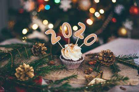 Christmas cupcake on the wooden table with fir tree branches, golden fir cones, cinnamon decoration and bokeh lights. Close up.