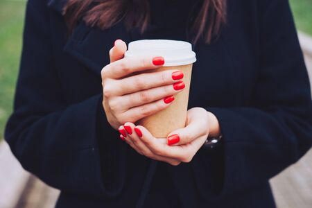 Hot drink in a craft plastic cup with a white cap in the hands of a young girl with a red manicure in a black coat close-up on the street in the fall afternoon.