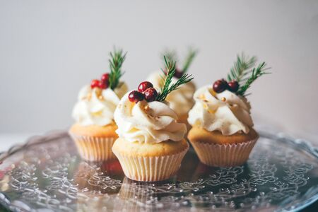 Beautiful christmas cupcakes with curd cream, cranberries and spruce branches on top on the glass table against a white wall.