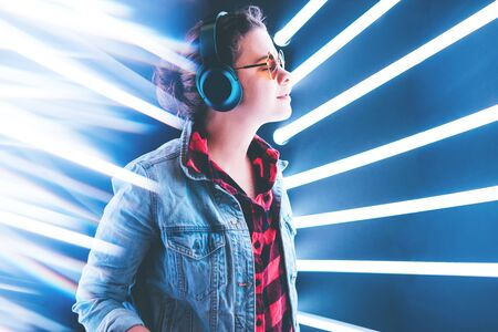 Girl stands in wireless headphones listening to music in a blue neon light. With the rays behind her. Archivio Fotografico