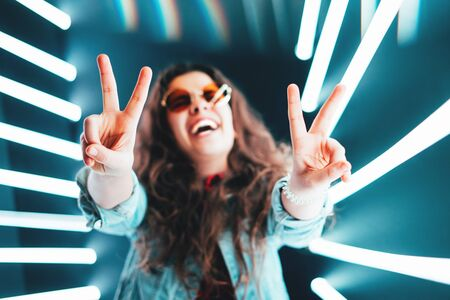 Cheerful cute smiling girl shows peace sign in round glasses at neon background.
