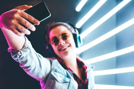 Portrait of modern young woman in headphones making selfie at the blue neon light.