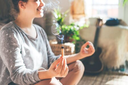 Young beautiful woman is meditating with palo santo in hand. Sits on the floor at home.