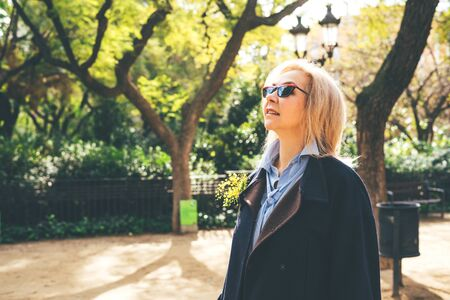 Beautiful adult lady blonde in sunglasses and in a blue coat standing in the spring alley and look up. With a sprig of mimosa.