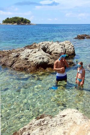 Pebble Beach: Man and girl with snorkeling mask in Adriatic sea, on Peljesac, Zuljana. Croatia