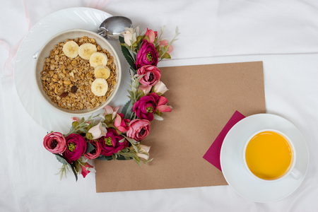 Breakfast in bed with muesli, fruit and orange juice with flowers and a card