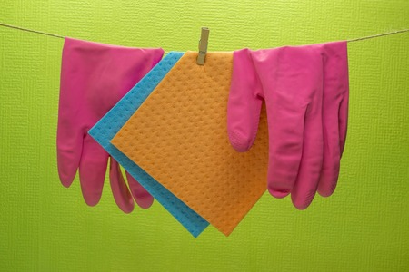 Kitchen sponges and rubber gloves hanging on rope