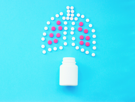 Lungs made of pills on blue background.