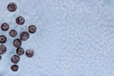 Ripe blueberry berries in blue water with air bubbles. Top view. Wallpapers