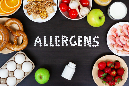 Food allergens as milk, oranges, tomatoes, garlic, shrimp, peanuts, eggs, apples and bread and strawberries on wooden table. Inscription food allergens.
