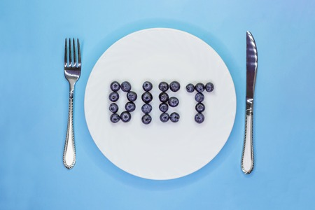 Inscription Diet made of blueberries on white plate with cutlery. Low calorie diet concept. Light blue background. Flat lay. Top view Zdjęcie Seryjne