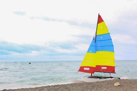Buntes Segelboot am europäischen Strand an einem bewölkten Tag