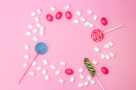 Flat lay composition with yummy lollipops and marshmallows and space for text on pink background. Frame of different sweets. Copy space 免版税图像