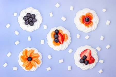 Meringue cakes with berries on a lavender background. Top view