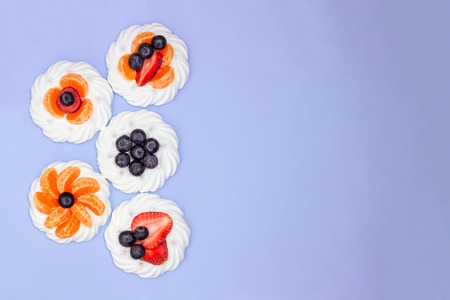 Meringue with blueberries, strawberries and tangerines on a lavender background. Minimal concept. Top view. Copy space.