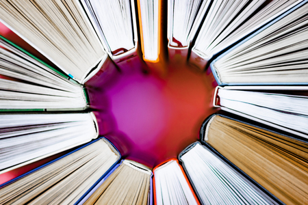 The heart of books on pink background. Top view. Love concept