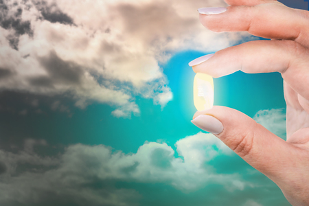 Woman is holding her fingers an antidepressant capsule against the blue sky. Exit from depression. Pill in hand 版權商用圖片