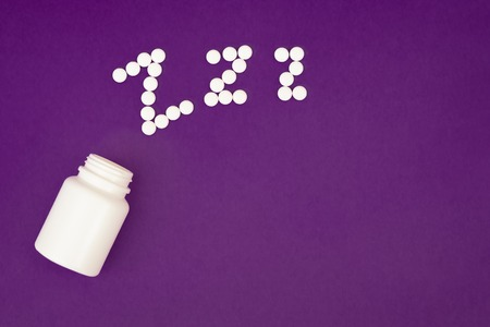 Inscription zzz made from white pills spilling from pill bottle on violet background 免版税图像