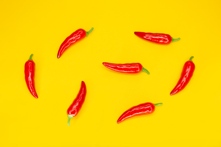 Red chilli peppers on yellow background. Ingredient of Mexican Cuisine. Flat lay. Top view