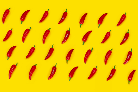 Red chilli peppers pattern on yellow background. Flat lay. Top view. Imagens