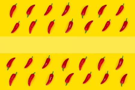 Red chili pepper frame on a yellow background with copy space. Ingredient of Mexican Cuisine. Top view.
