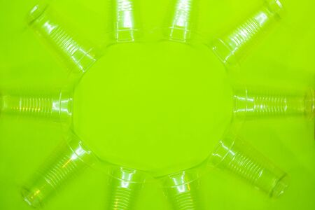 Round frame of trasparent plastic disposable cups on green background. Empty space in the center of the image. Top view. Stock Photo