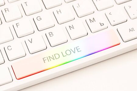 Homosexual online dating concept. White keyboard with rainbow button and an inscription find love. Close-up view Reklamní fotografie