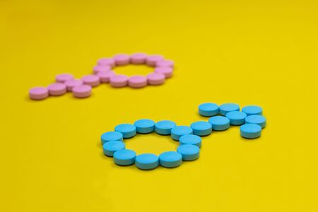 Blue pills in the form of a gender signs of Mars and Venus on a yellow background. Medical concept. Stock Photo