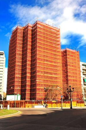 tall building completely covered by a tarp orange for rehabilitation