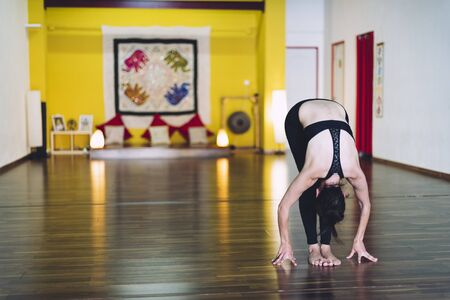 Woman doing yoga in a yoga school with her hands resting on the floor. Concept of yoga