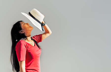 Brunette Latin woman in profile holding a hat in front of her face with one hand protecting herself from the sun. Copy space