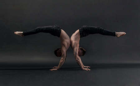 two twin brothers in black jeans with a torso perform acrobatic elements, black background