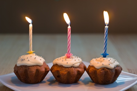 Three homemade muffins with burning candles photo