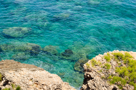 Crystal clear transparent turquoise water of Mediterranean sea near rocky shore in Turkey, Antalya region